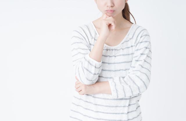 顎に手を当て悩む女性