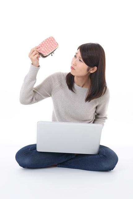 財布を悩ましげに見る女性