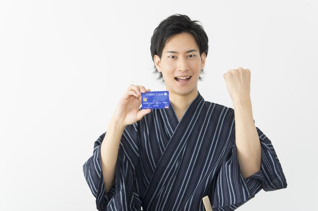 クレジットカードを持って喜ぶ男性